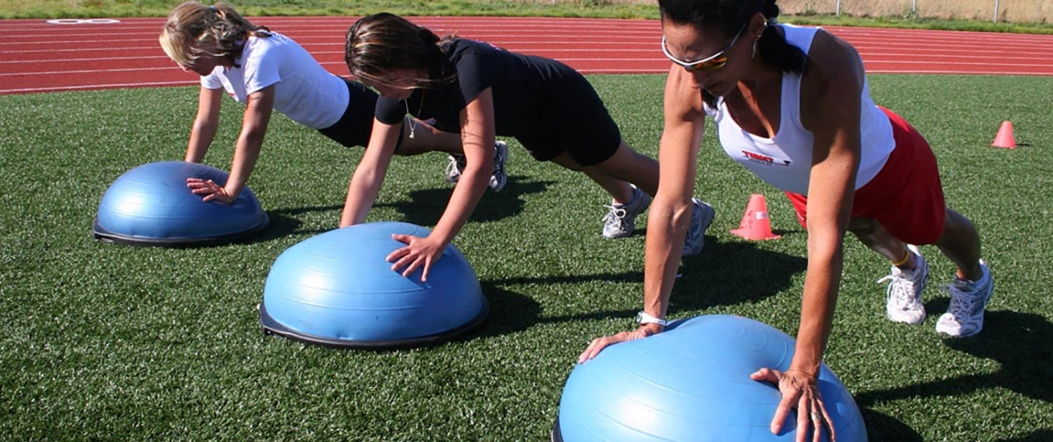 Beyond Fitness creator Michele Vaughan demonstrates a stabilization exercise on the Bosu