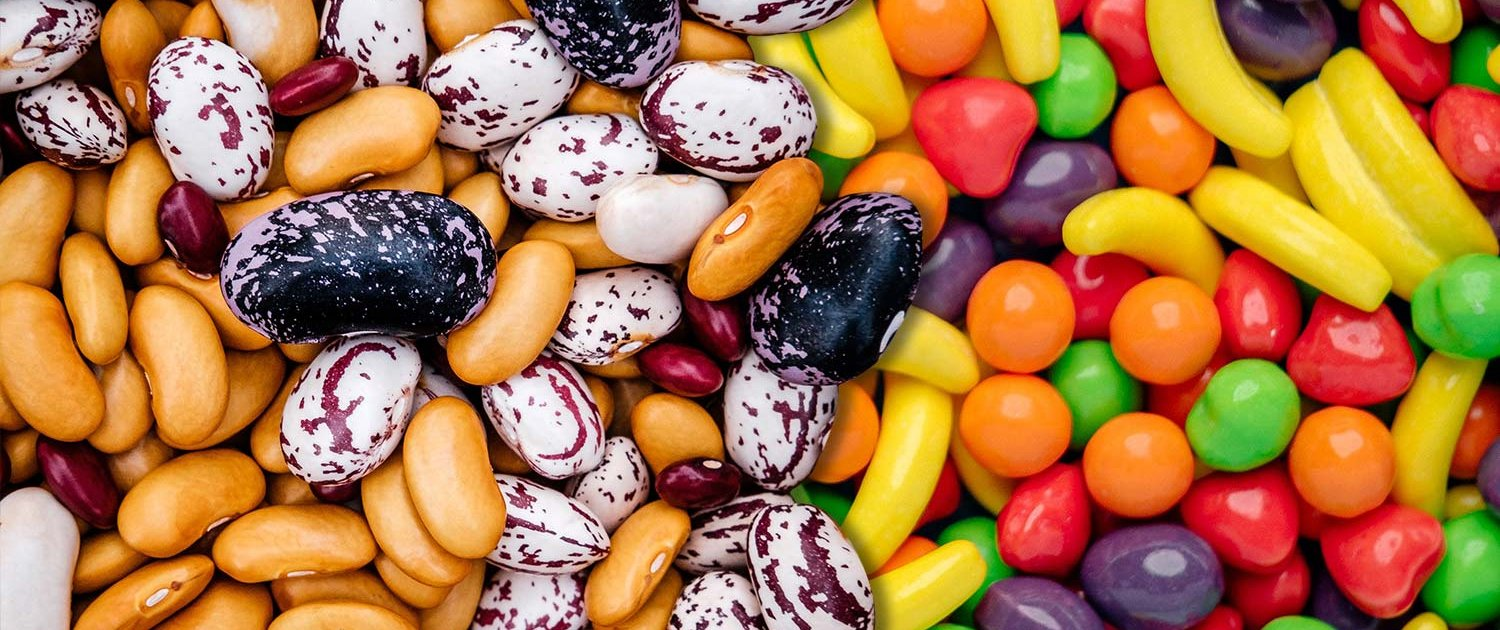 Close up view of a pile of beans on the left side, composited with a pile of candies on the right.