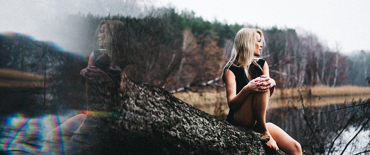 Woman seen through a window sits on a tree trunk, looking into the distance.